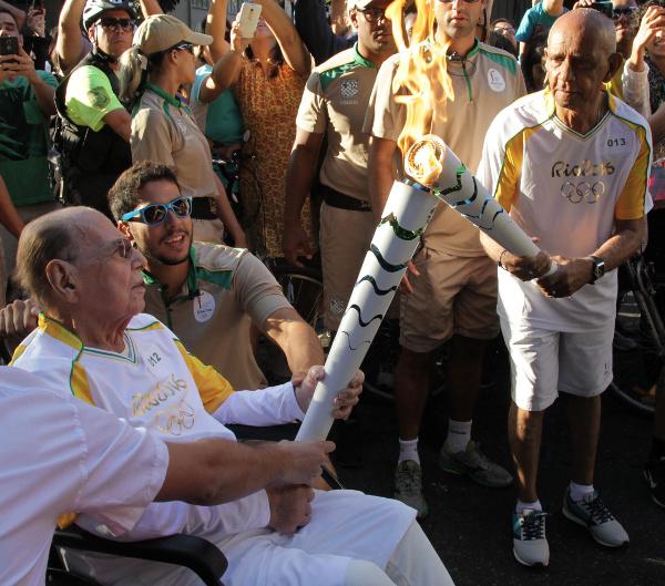 At Palácio da Cidade, plastic surgeon Ivo Pitanguy hands over the Olympic torch to Gyleno dos Santos, waiter at Mayor Eduardo Paes's Office / Photo Credit: Ricardo Cassiano